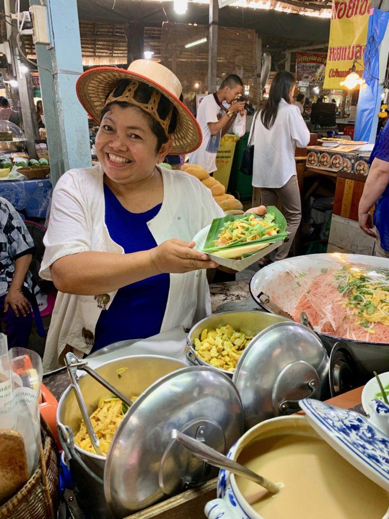 Il mercato galleggiante: signora che cucina sorridendo