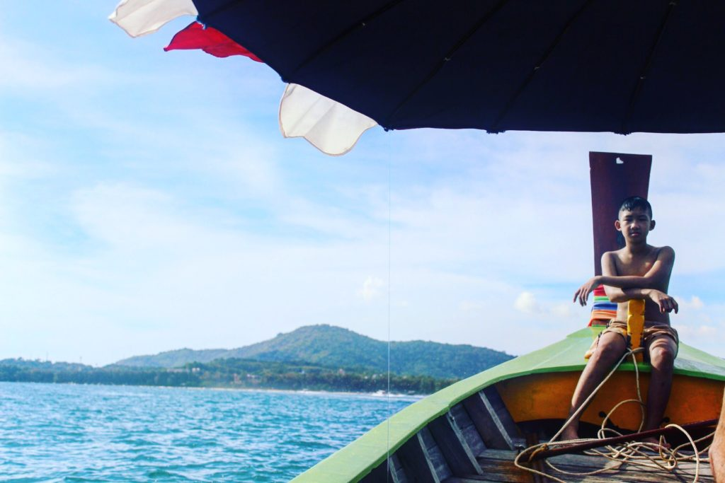 Bambino sulla barca di legno