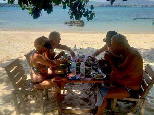 persone che pranzano in spiaggia