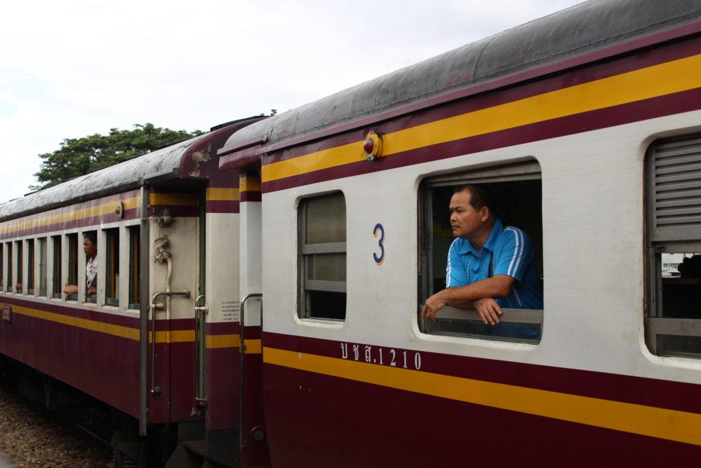Come muoversi in Thailandia: uomo al finestrino del treno